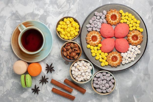 Bovenaanzicht kopje thee met snoepjes, koekjes en taarten op wit bureau