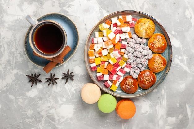Bovenaanzicht kopje thee met snoepjes macarons en kleine cakes op witte ondergrond