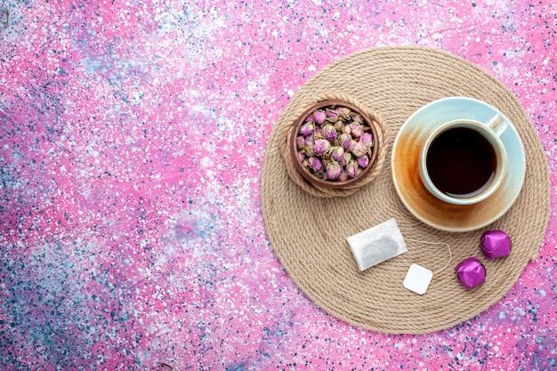 Bovenaanzicht kopje thee met snoepjes op de roze achtergrond.