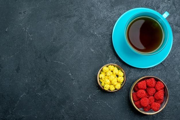 Bovenaanzicht kopje thee met snoepjes op grijze bureau kandijsuiker zoete thee