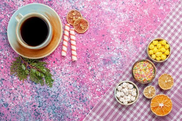 Bovenaanzicht kopje thee met snoepjes op het roze bureau snoep thee drinken zoete suiker confituur kleur