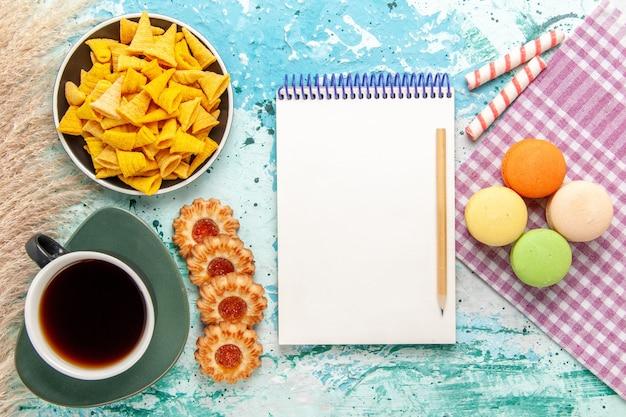 Bovenaanzicht kopje thee met suikerkoekjes en chips op lichtblauwe achtergrond cookie biscuit suiker zoete thee cake taart