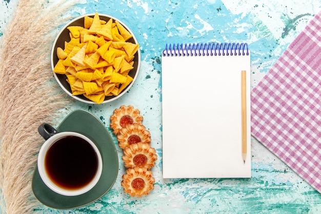 Bovenaanzicht kopje thee met suikerkoekjes en chips op lichtblauwe ondergrond