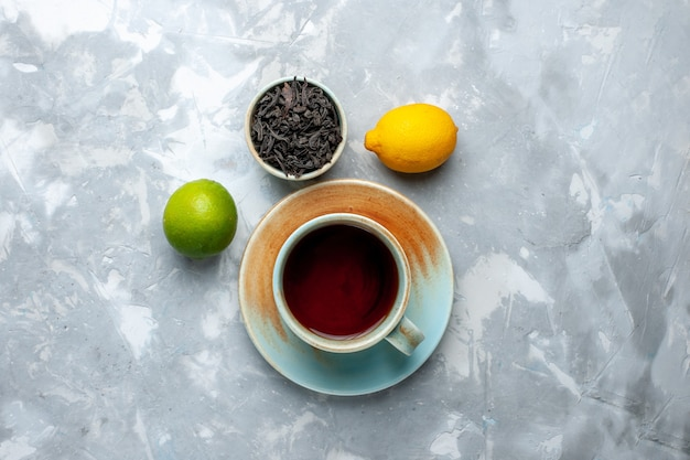 Bovenaanzicht kopje thee met verse citroenen en gedroogde thee op de lichttafel, thee fruit citrus kleur