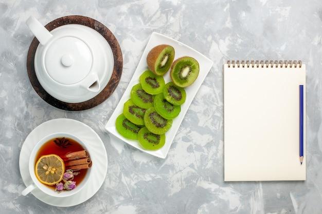 Bovenaanzicht kopje thee met verse kiwi's en blocnote op witte ondergrond
