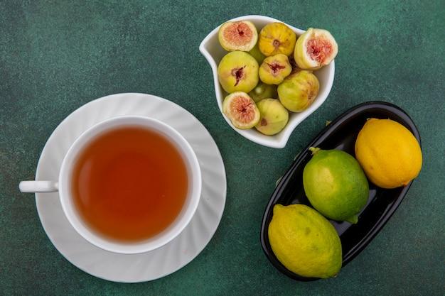 Bovenaanzicht kopje thee met vijgen en limoenen en citroen op groene achtergrond