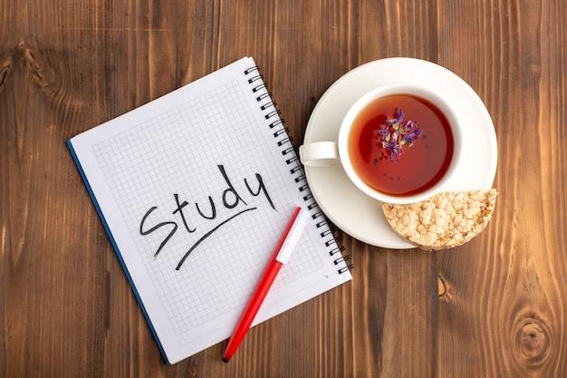 Bovenaanzicht kopje thee met voorbeeldenboek en potlood op bruin bureau