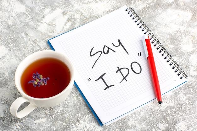 Bovenaanzicht kopje thee met voorbeeldenboek en potlood op wit bureau