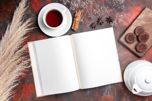 Bovenaanzicht kopje thee met voorbeeldenboek op donker bureau