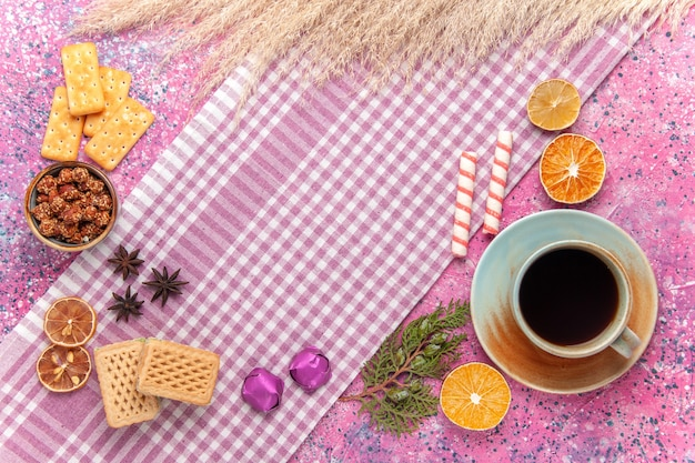 Bovenaanzicht kopje thee met wafels en crackers op roze
