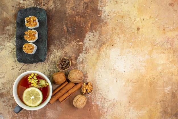 Bovenaanzicht kopje thee met walnoten snoepjes op houten bureau