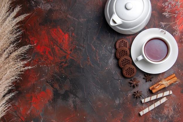 Bovenaanzicht kopje thee met waterkoker en koekjes op de donkere tafel