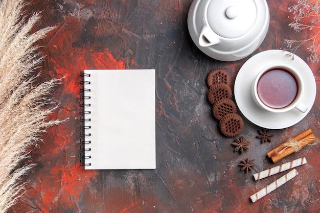 Bovenaanzicht kopje thee met waterkoker en koekjes op donker bureau