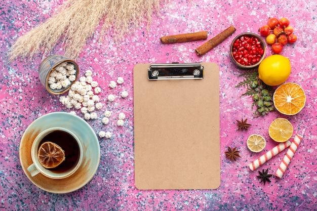 Bovenaanzicht kopje thee met witte zoete confitures blocnote en kaneel op roze oppervlak