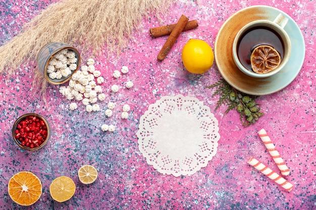 Bovenaanzicht kopje thee met witte zoete confitures citroen en kaneel op roze oppervlak