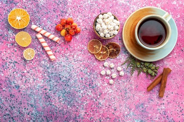 Bovenaanzicht kopje thee met witte zoete confitures op het roze bureau