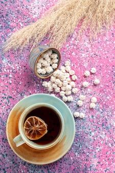 Bovenaanzicht kopje thee met witte zoete confitures op het roze oppervlak
