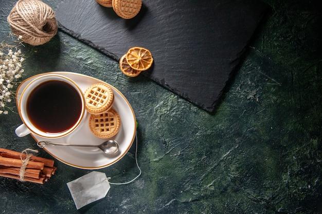 Bovenaanzicht kopje thee met zoete koekjes op donkere achtergrond