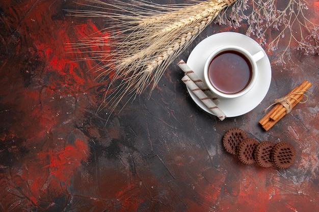 Bovenaanzicht kopje thee met zoete koekjes op donkere tafel