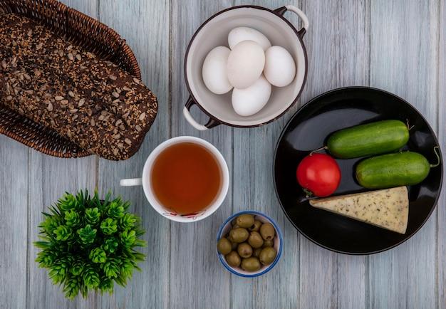 Bovenaanzicht kopje thee met zwart brood, kaas, komkommers en tomaat op een bord en olijven met kippeneieren in een pan op grijze achtergrond