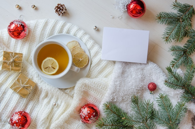 Bovenaanzicht kopje thee versierd met gebreide sjaal, dennentakken en dennenappels.