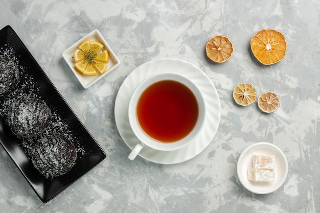 Bovenaanzicht kopje thee warme drank met chocoladetaart op licht-wit bureau
