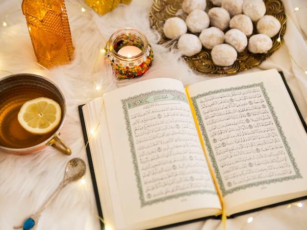 Bovenaanzicht koran omgeven door thee en gebak