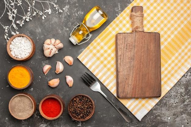 Bovenaanzicht kruiden bord op het geruite tafelkleed knoflook fles olie kruiden vork