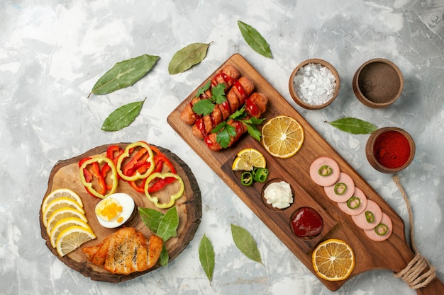 Bovenaanzicht kruiden en groenten met citroenen op licht wit bureau