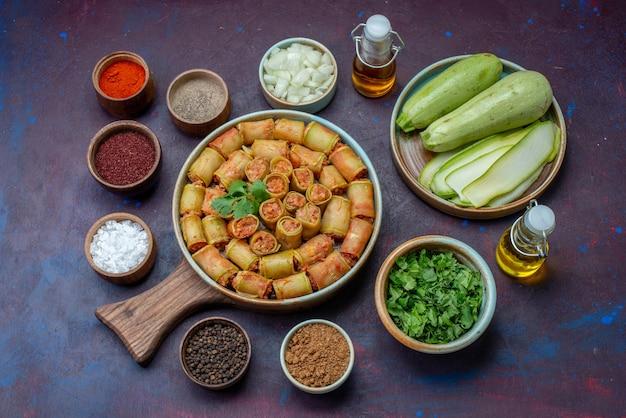 Bovenaanzicht kruiden in potten zout peper met verse pompoenen vleesrolletjes op het donkerpaarse oppervlak