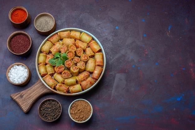 Bovenaanzicht kruiden in potten zout peper met vleesrolletjes op het donkerpaarse oppervlak