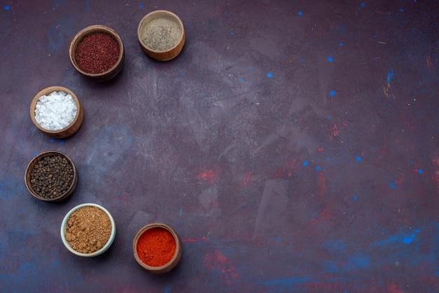 Bovenaanzicht kruiden in potten zout peper op het donkerpaarse oppervlak