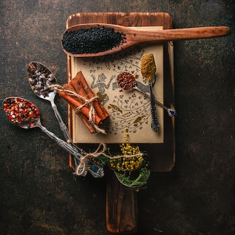 Bovenaanzicht kruiden met kaneel en peper en lepel in houten plaat