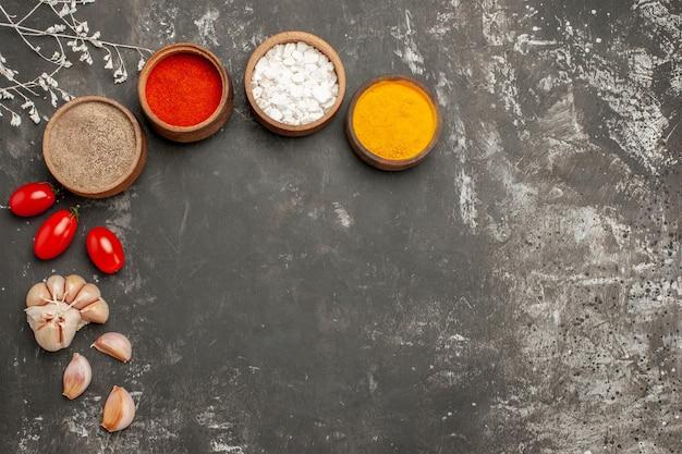 Bovenaanzicht kruiden op tafel kleurrijke kruiden in kommen tomaten en knoflook op de zwarte tafel