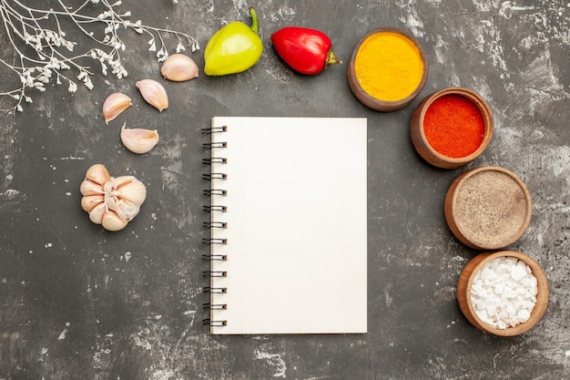 Bovenaanzicht kruiden op tafel knoflook kleurrijke kruiden bal peper op de donkere tafel