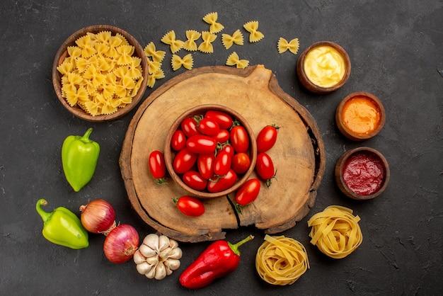 Bovenaanzicht kruiden pasta in kom drie soorten saus knoflook ui rode en groene paprika naast de tomaten op de houten snijplank