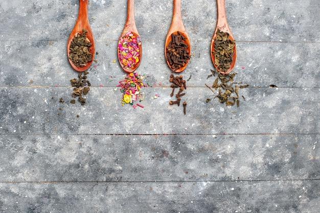 Bovenaanzicht kruiden samenstelling verschillend gekleurd binnen lepels op de grijze rustieke bureau thee droge plant kleur