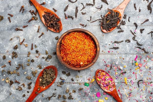 Bovenaanzicht kruiden samenstelling verschillend gekleurd op grijze bureau thee droge plant kleur