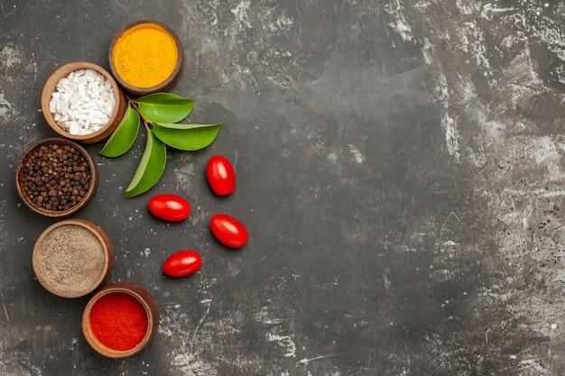 Bovenaanzicht kruiden vijf kommen met kleurrijke kruiden laat tomaten aan de linkerkant van de tafel