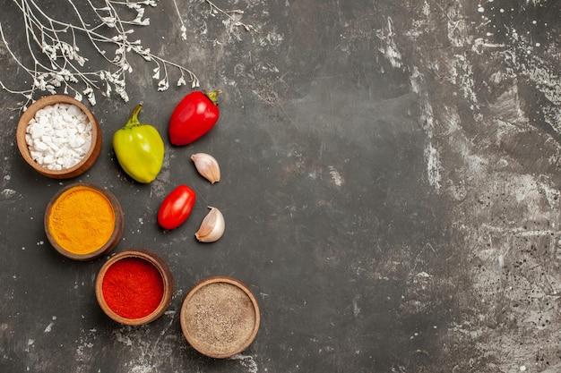 Bovenaanzicht kruidenkommen met kleurrijke kruiden, tomaten, knoflook en peper op de donkere tafel