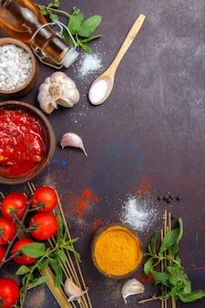 Bovenaanzicht kruiderijen en saus met tomaten op donkere achtergrond maaltijd pittige warme voedselkleur