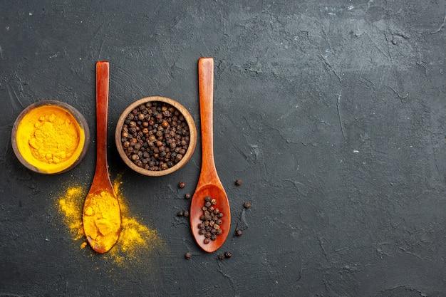 Bovenaanzicht kurkuma zwarte peper in kleine kommen in houten lepels op donkere tafel met vrije ruimte