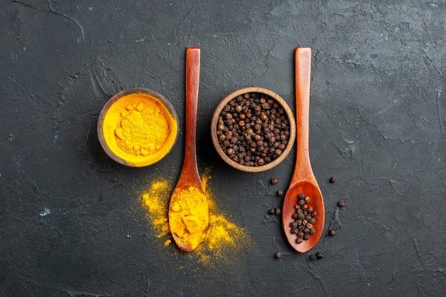 Bovenaanzicht kurkuma zwarte peper in kleine kommen in houten lepels op donkere tafel vrije ruimte