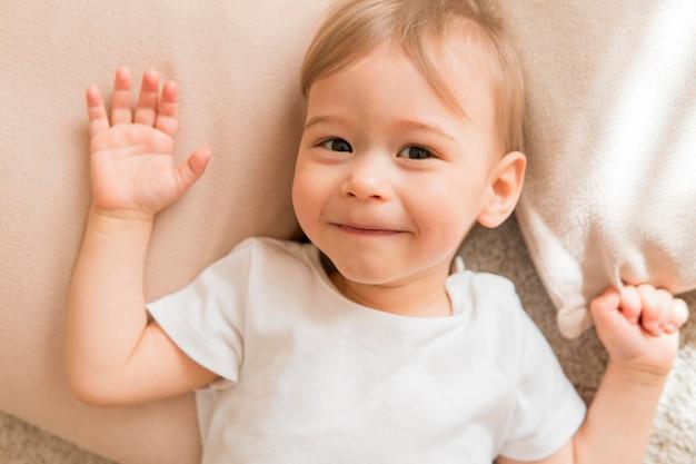 Bovenaanzicht lachende baby op kussen