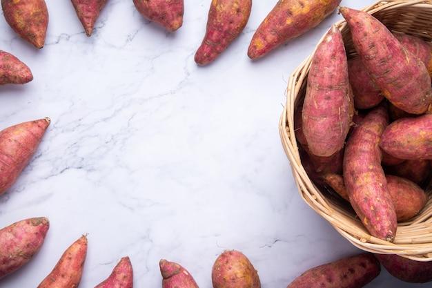 Bovenaanzicht lag de rode zoete aardappelen in vlakke mand, ruwe voedselvertoning op witte marmeren achtergrond met exemplaarruimte