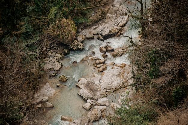 Bovenaanzicht landschap van azuurblauwe bos rivier stroomt onder rotsen in martvili canyon
