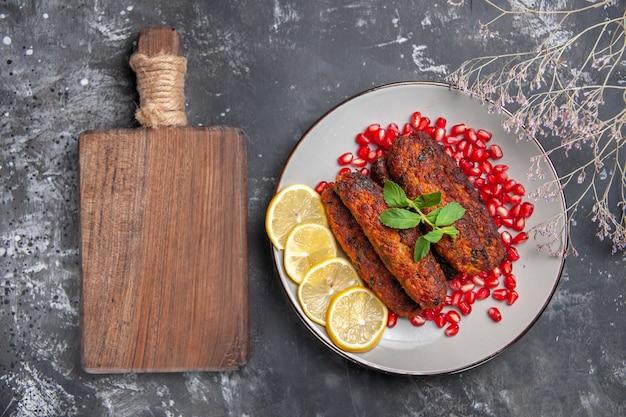Bovenaanzicht lange vleeskoteletten met citroen en granaatappels