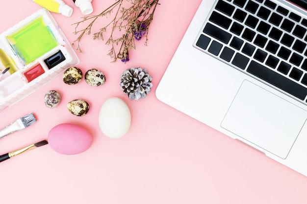 Bovenaanzicht laptop achtergrond en verf set voorbereiden op pasen op roze achtergrond, paaseieren