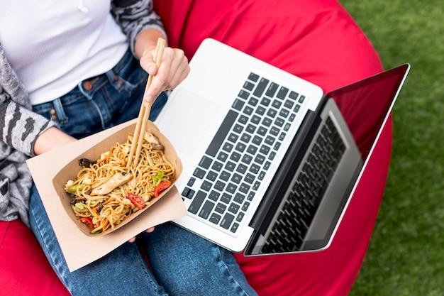 Bovenaanzicht laptop en fast food in het park