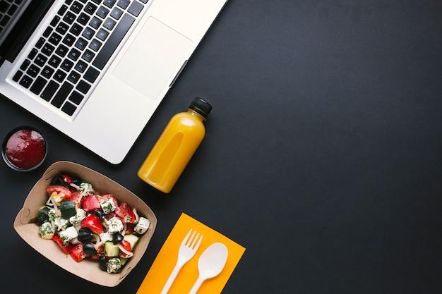 Bovenaanzicht laptop en salade op zwarte achtergrond